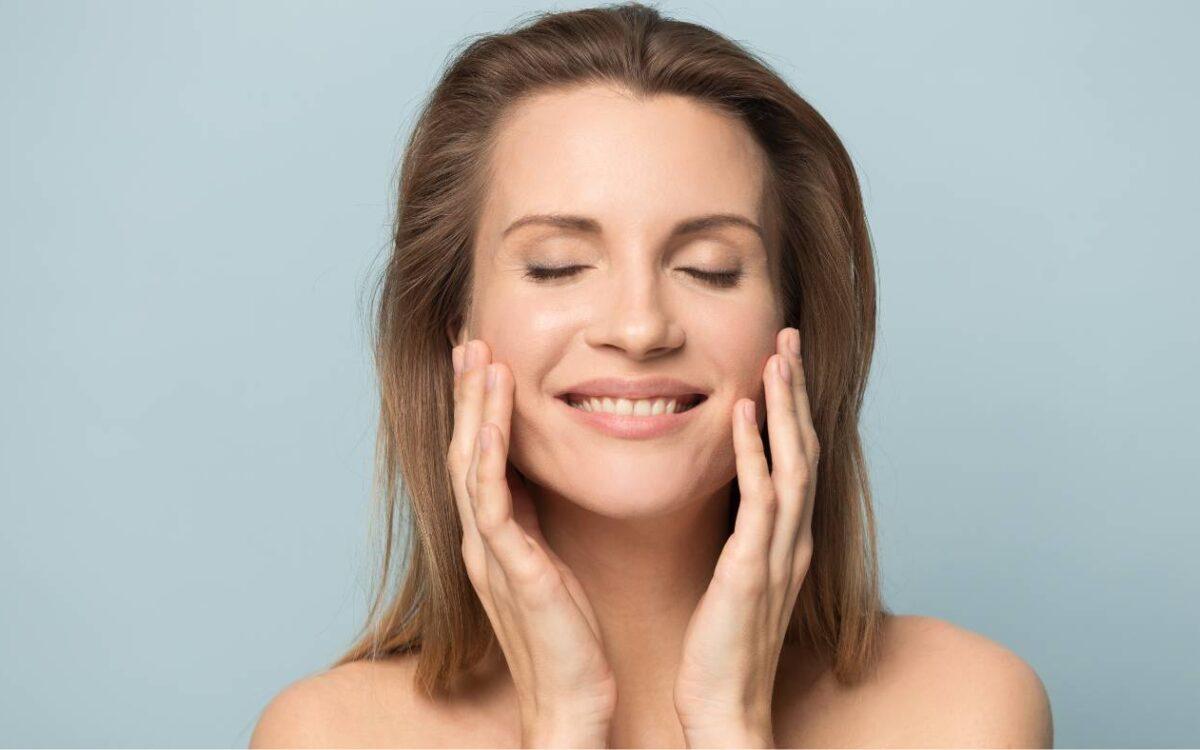 mujer feliz tocando su cara tras el tratamiento de rejuvenecimiento facial