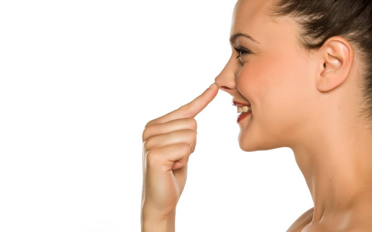 mujer tocando su nariz con el dedo
